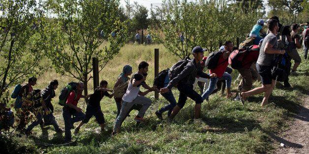 People run amid scuffles with the Croatian police in Tovarnik, Croatia, Thursday, Sept. 17, 2015. Hundreds...