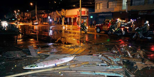 Police patrol a debris strewn street in Valparaiso, Chile, after a tsunami, caused by an earthquake hit...