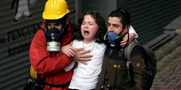 People help a child affected by teargas as riot police use water cannons and teargas to disperse thousands...