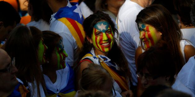 Young girls with their face painted with a pro-independence Catalan flag, known as the Estelada flag,...