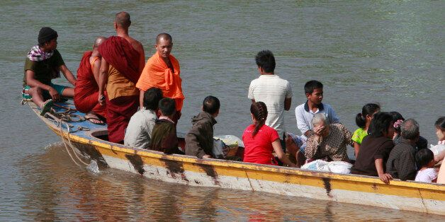 A boat carrying last batch of Myanmar refugees back home cruises on the Moei river in Mae Sot, Thailand...