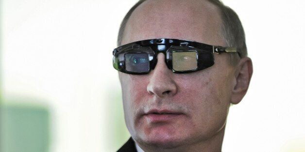 Russian President Vladimir Putin wears special glasses as he visits a research facility of the St. Petersburg...