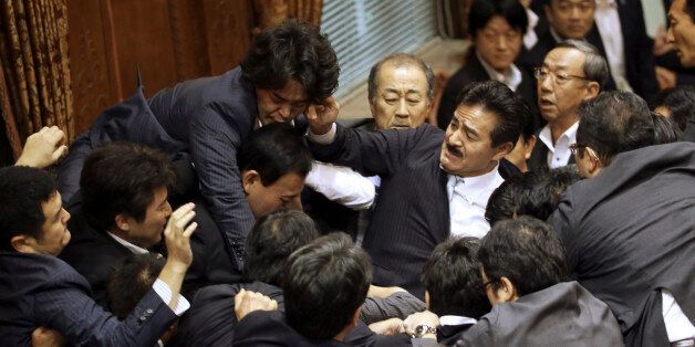 Opposition lawmakers surge toward the chairman's seat to protest as ruling party colleagues rush in...