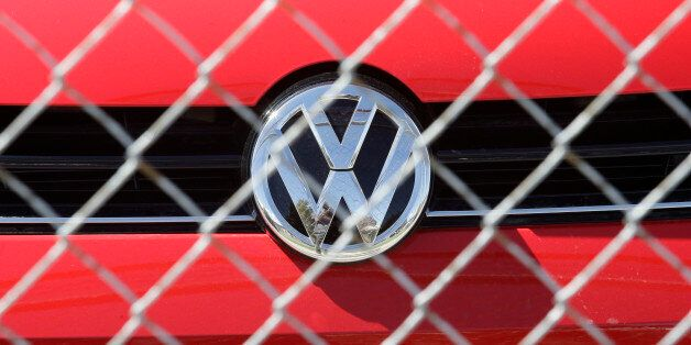 A Volkswagen diesel sits behind a security fence on a storage lot near a VW dealership Wednesday, Sept....