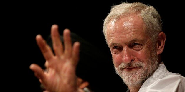 British lawmaker Jeremy Corbyn waves to a member of the audience prior to addressing a meeting during...