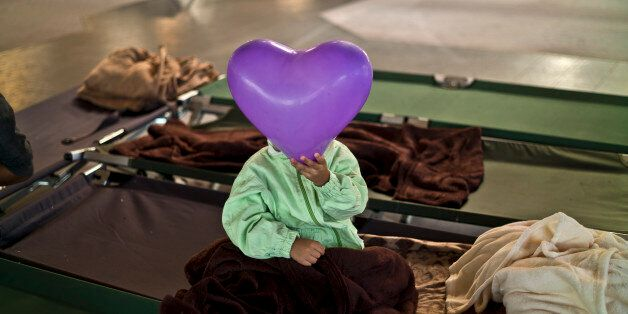 An Afghan refugee child covers his face with a balloon while he and other migrants spent the night in...