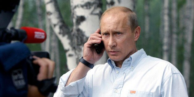 Prime Minister Vladimir Putin speaks on a cell phone with President Dmitry Medvedev, during a visit to...