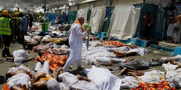 A muslim pilgrim walks through the site where dead bodies are gathered in Mina, Saudi Arabia during the...
