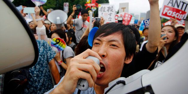 Protesters shout slogans during a rally in front of the National Diet building in Tokyo, Sunday, Aug....