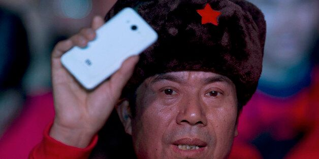 A fan of Xiaomi smartphone holds up one of the phones during a product unveiling event of the Chinese...