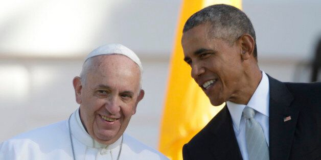 President Barack Obama leans over to talk to Pope Francis during a state arrival ceremony on the South...