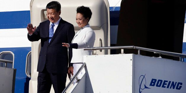Chinese President Xi Jinping, left, and his wife Peng Liyuan wave on their arrival Tuesday, Sept. 22,...