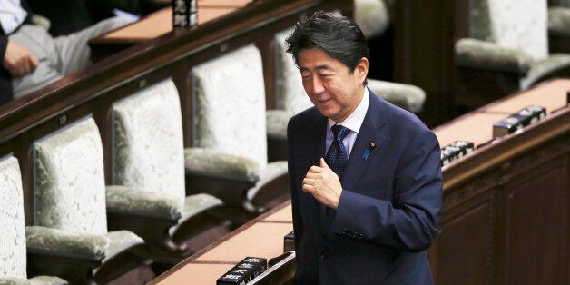 Japanese Prime Minister Shinzo Abe smiles during a vote of opposition-submitted no-confidence motion...
