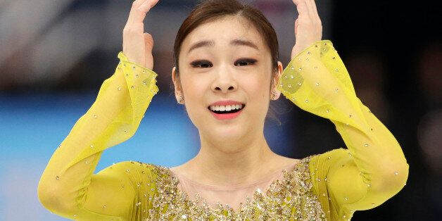 Yuna Kim of South Korea reacts after completing her routine in the women's short program figure skating...