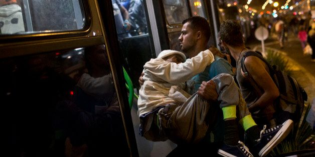 A man helps a disabled person get on a bus provided by Hungarian authorities for migrants and refugees...
