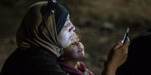 헝가리 국경지대 로즈케에서 한 소녀가 엄마의 휴대폰 화면을 들여다보고