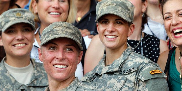 U.S. Army First Lt. Shaye Haver, center, and Capt. Kristen Griest, right, pose for photos with other...