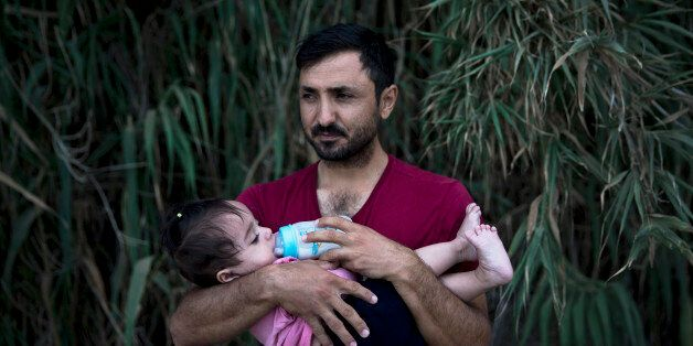 A Syrian refugee feeds milk to his daughter after they arrived on a dinghy, from Turkey to Lesbos island,...