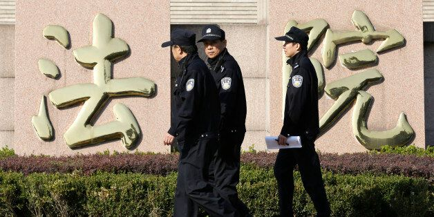 Policemen walk past Chinese characters