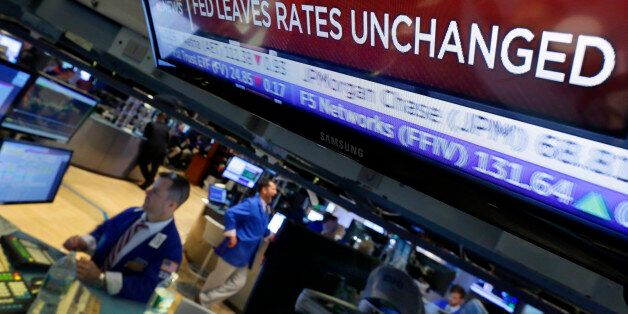 A television screen on the floor of the New York Stock Exchange shows the decision of the Federal Reserve,...