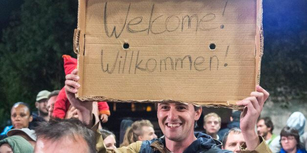 Am man holds a cardboard with a 'Welcome' slogan during the arrival of refugees at the train station...