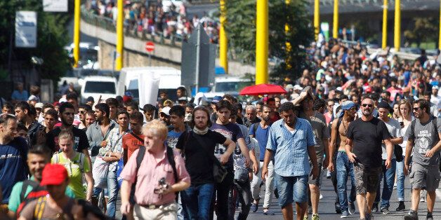 Migrants walk along the Hegyalja Street in Budapest, Hungary, Friday, Sept. 4, 2015. Several thousand...