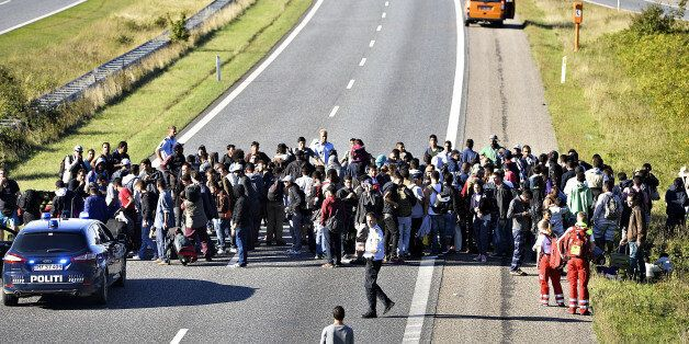 A group of refugees and migrants who were walking north stand on the highway in southern Denmark on Wednesday,...