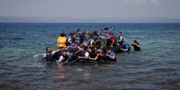 Refugees and migrants arrive on a dinghy after crossing from Turkey to Lesbos island, Greece, Friday,...