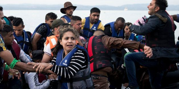 Syrian refugees arrive on a dinghy after crossing from Turkey to Lesbos island, Greece, Wednesday, Sept....
