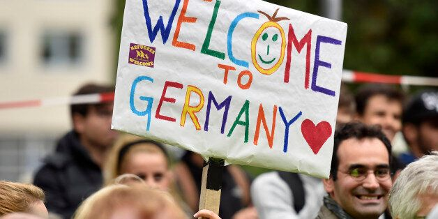 People welcome refugees with a banner reading 'welcome to Germany' in Dortmund, Germany, Sunday, Sept....