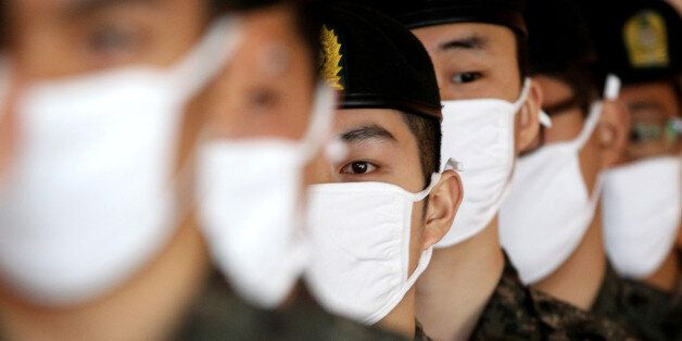 South Korean army soldiers wait to carry out caskets containing remains of Chinese soldiers to transport...