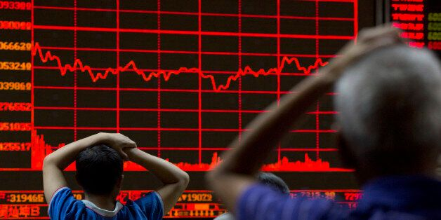 Investors monitor a display showing the Shanghai Composite Index at a brokerage in Beijing, Monday, Aug....