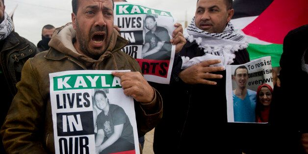 Palestinian demonstrators hold portraits of Kayla Mueller, a 26-year-old American who died while being...