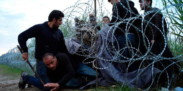 FILE - In this Aug. 26, 2015, file photo, Syrian refugees cross into Hungary underneath the border fence...