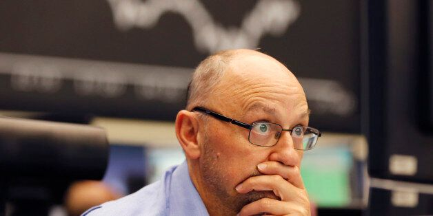 A trader watches his screens when the curve of the German stock index DAX fell under 10,000 points at...
