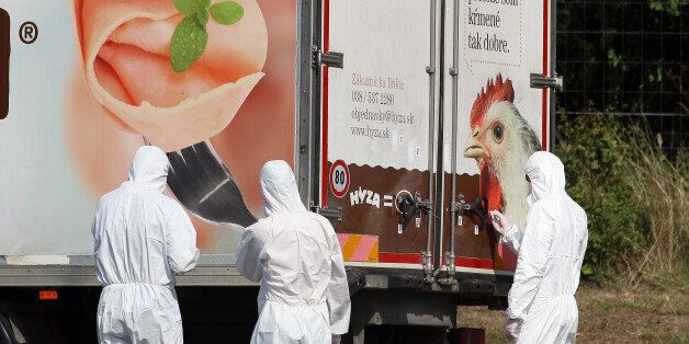 Investigators stand near a truck that stands on the shoulder of the highway A4 near Parndorf south of...