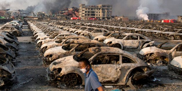 In this photo taken Thursday, Aug. 13, 2015, a man walks past the charred remains of new cars at a parking...