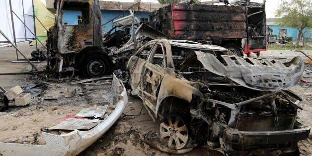Burned vehicles remain in the Industrial Stadium a day after a series of bombs exploded in eastern Baghdad,...