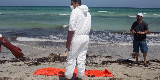 Workers for the Red Crescent pull dead migrants from the water and place them in orange-and-black body...
