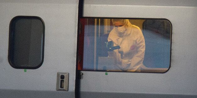 ALTERNATE CROP TO REB103 - A police officer videos the crime scene inside a Thalys train at Arras train...