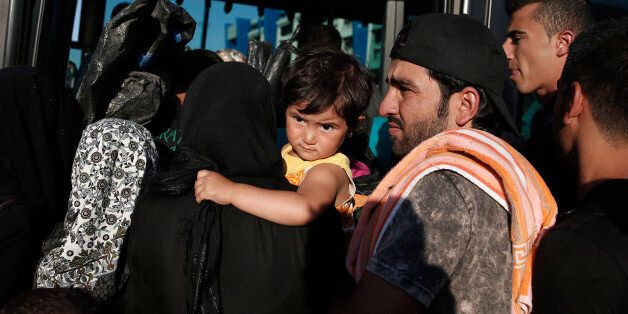 Refugees try to get in a bus after they arrived on a ferry at the port of Piraeus, near Athens, Saturday,...