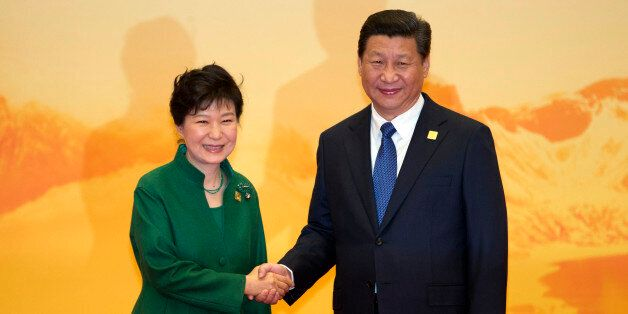 South Korean President Park Geun-hye shakes hands with Chinese President Xi Jinping during a welcome...