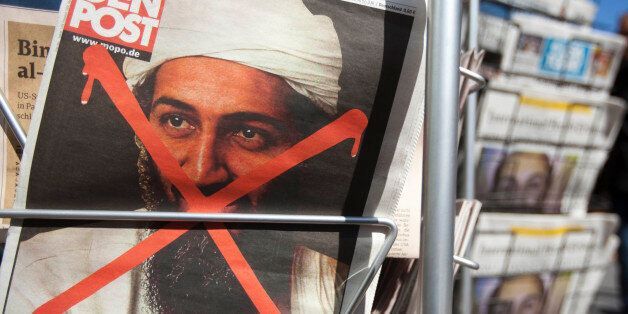 People pass newspapers front pages with the report of Osama bin Laden's death, at a newsstand in Berlin...