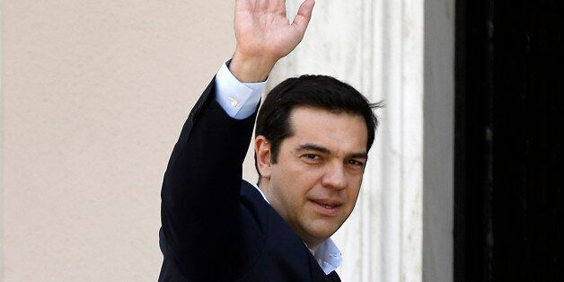 Greece's Prime Minister Alexis Tsipras waves to the media as he arrives at Maximos Mansion after a swearing...