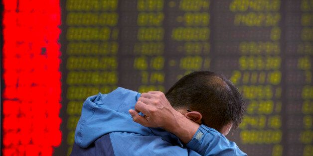 A Chinese investor monitors stock prices at a brokerage house in Beijing, Tuesday, Aug. 25, 2015. China's...