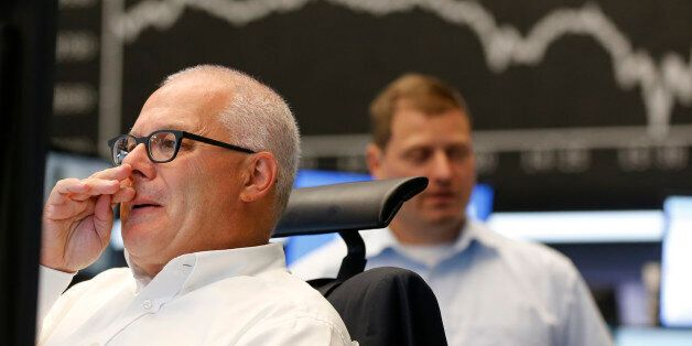 A trader wipes his nose when the curve of the German stock index DAX fell under 10,000 points at the...