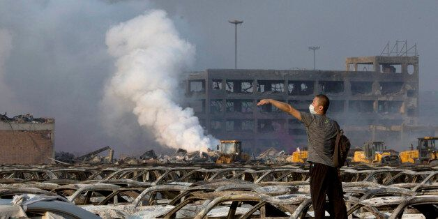 In this photo taken Thursday, Aug. 13, 2015, a man walks through the site of an explosion at a warehouse...