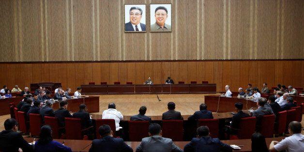 North Korea's General Reconnaissance Bureau Director Kim Yong Chol, center left, sits under the portraits...