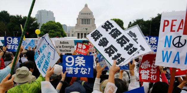 Protesters hold anti-war placards in front of the National Diet building during a rally in Tokyo, Sunday,...