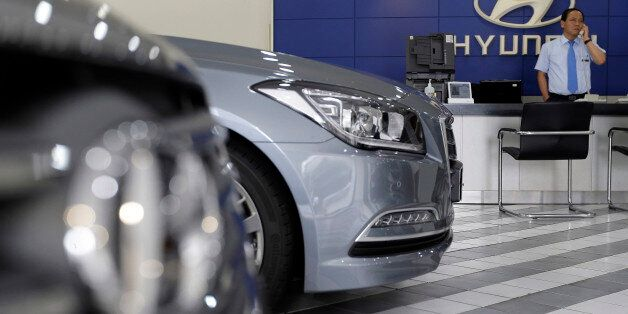 An employee of Hyundai Motor Co. works at the company's showroom in Seoul, South Korea, Thursday, July...
